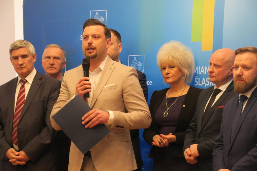 Pamiątkowa fotka na ściance, pierwszy z lewej Zbigniew Szaleniec, trzecia z prawej Krystyna Wróbel. Przemawia Rafał Piech.