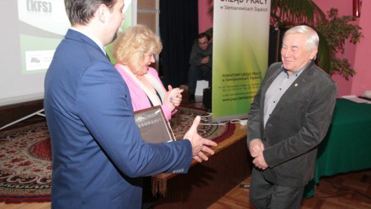 Jan Ostrowski, pierwszy z prawej, odbiera nagrodę z rąk prezydenta Rafała Piecha i dyrektor Powiatowego Urzędu Pracy Hanny Becker.