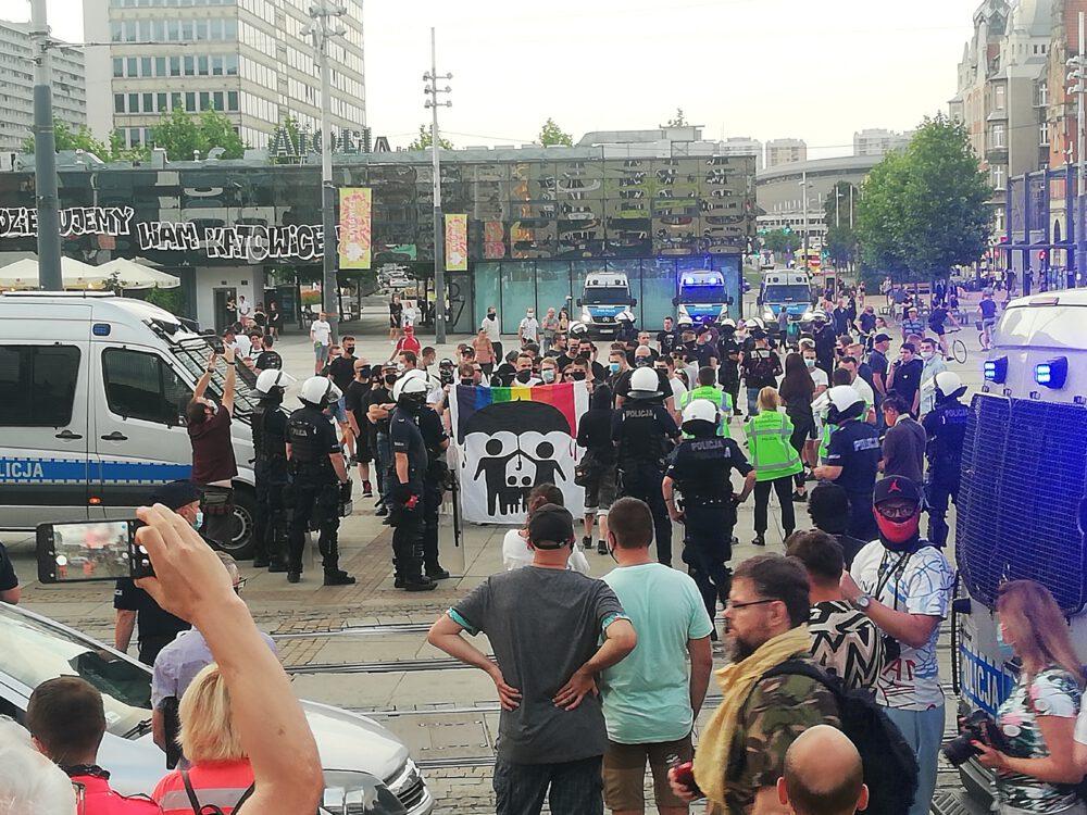 ... grupka antydemonstrantów w otoczeniu policji
