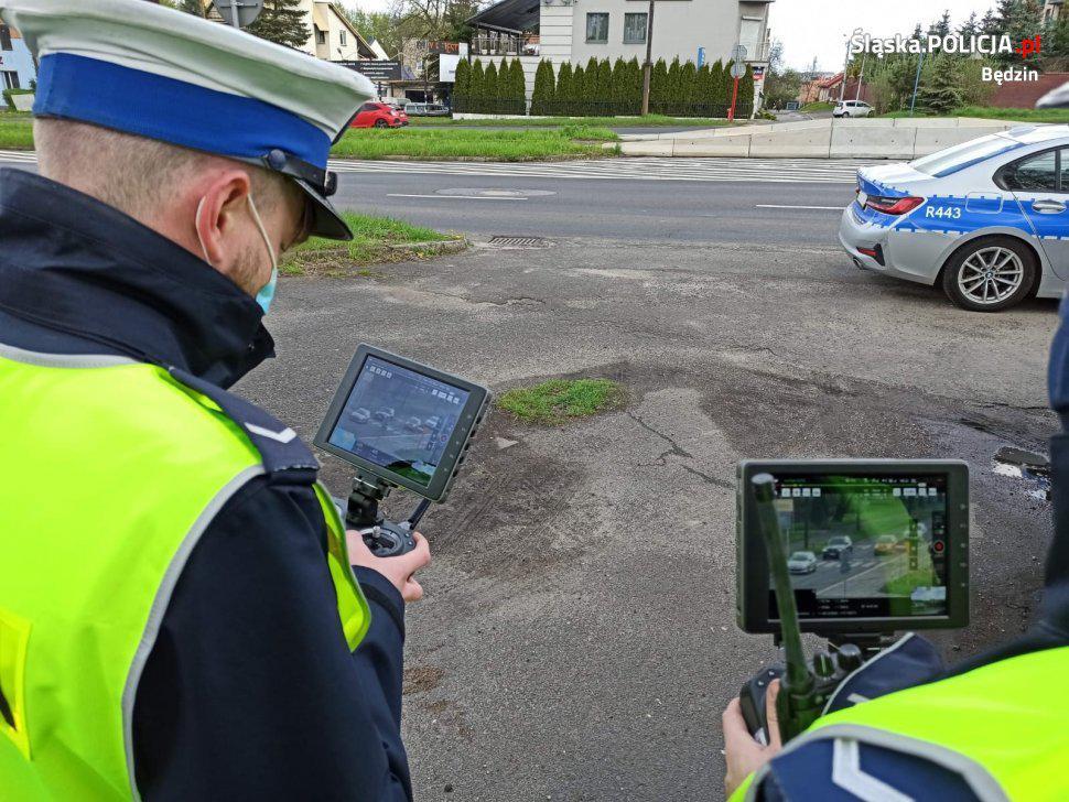 policjanci oglądają obraz z drona na tabletach