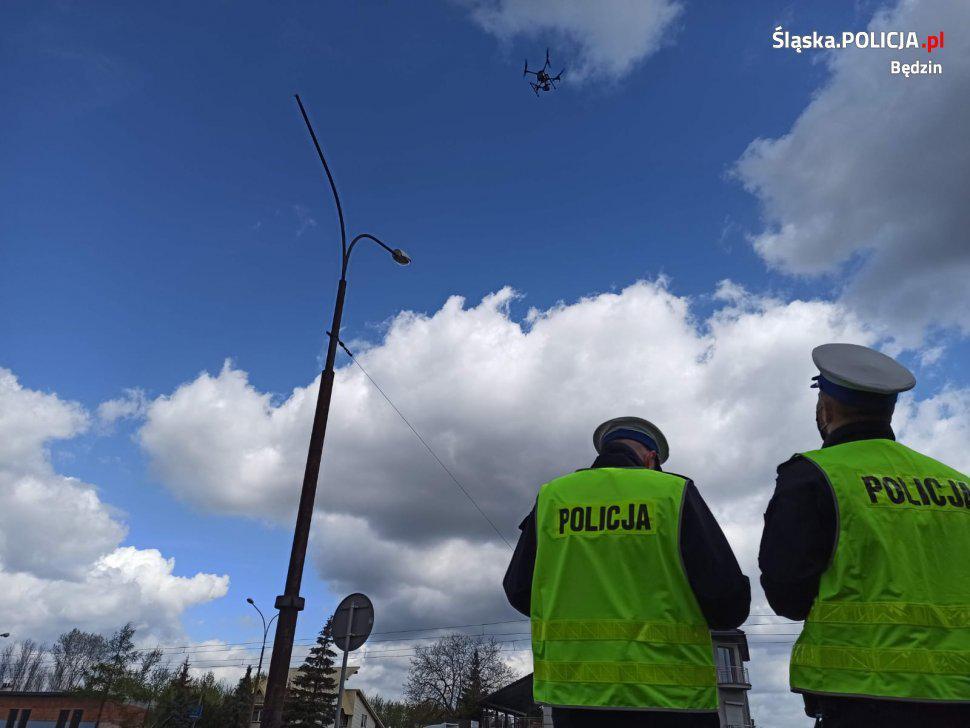 policjanci patrzą na drona
