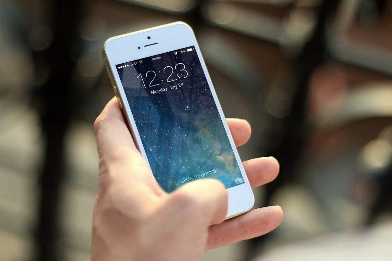 ręka z telefonem a na nim godzina czasu
