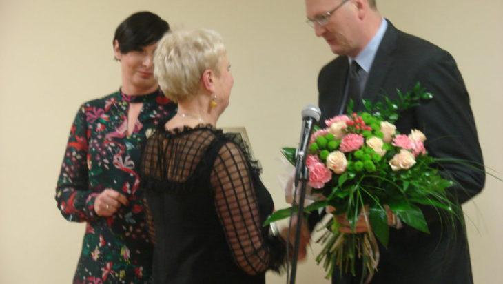 Adam Cebula przewodniczący RM składa gratulacje na ręce Wiesławy Szlachty, dyrektorki MBP